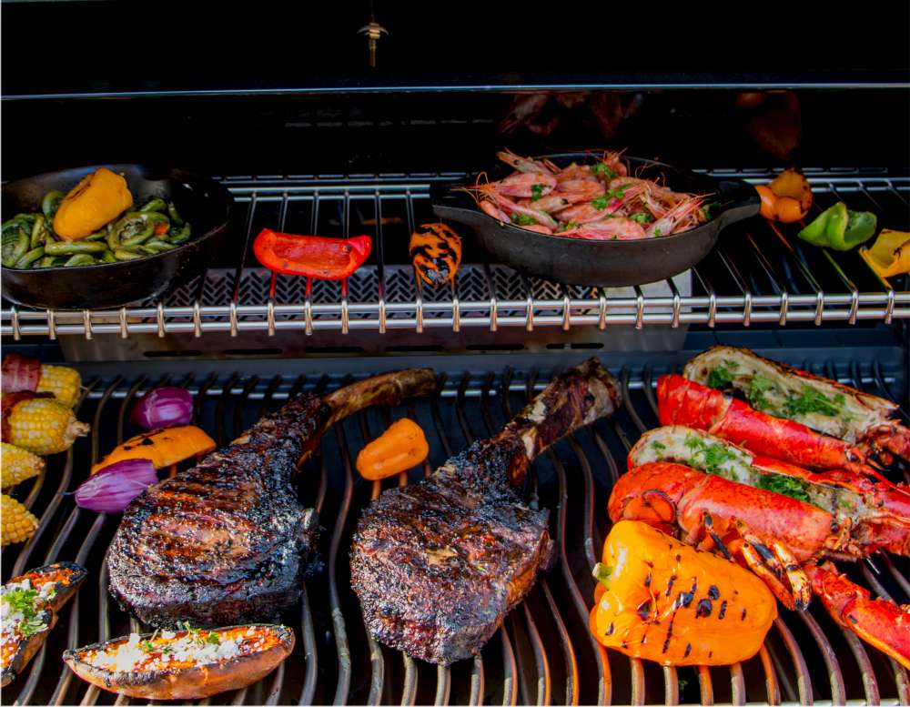 Perfectly cooked Tomahawk steak on the BBQ with vegetables and lobsters. How to cook the perfect Tomahawk steak?